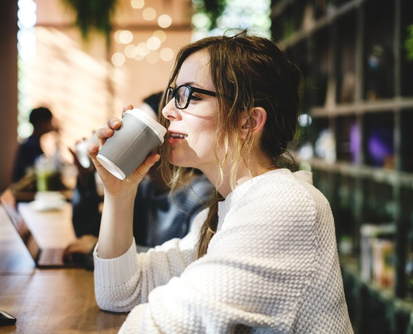Mujer con buena imagen sonriendo y tomando café