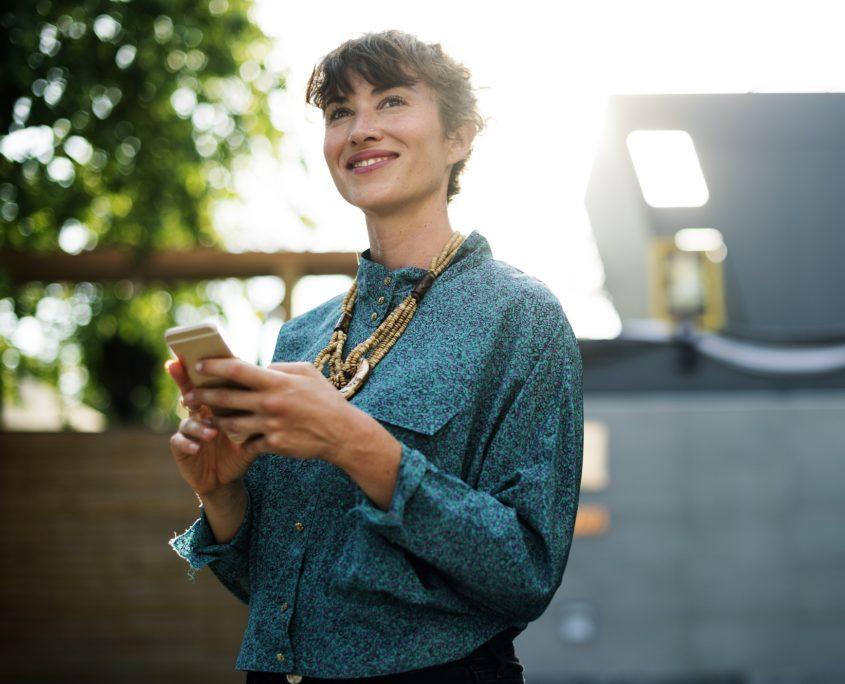 Mujer con buena imagen mirando su móvil y sonriendo